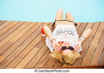 blonde woman by the pool on holiday