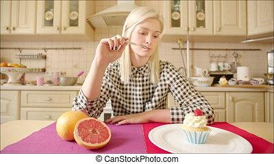 Blonde Woman Choosing between Fruit and Pastry