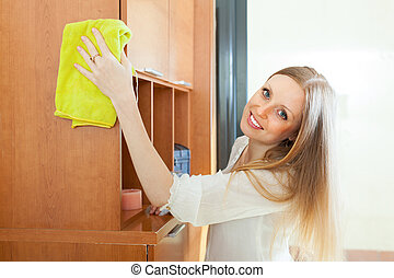 Blonde woman cleaning furniture