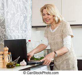 Blonde woman cooking with notebook