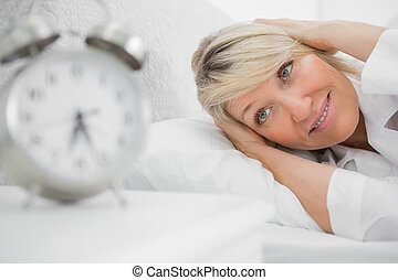 Blonde woman covering her ears from alarm clock noise