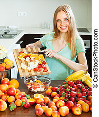 blonde woman cutting fruits for salad