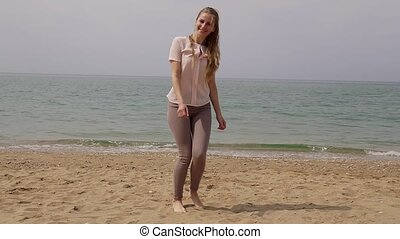 blonde woman dances and laughs at the beach