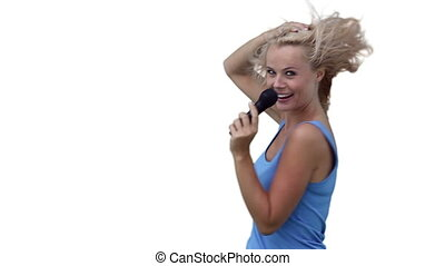 Blonde woman dancing as she sings into a microphone