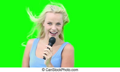 Blonde woman dancing while singing with a microphone