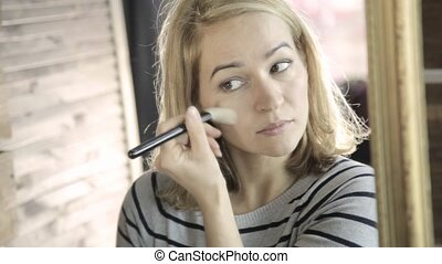 Blonde woman doing everyday makeup in front of mirror, puts...
