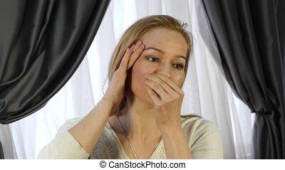 blonde woman doing self-massage, anti-aging facial massage...