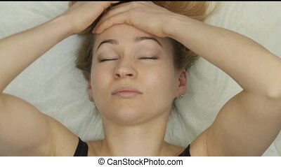 blonde woman doing self-massage, facial massage lying in bed...