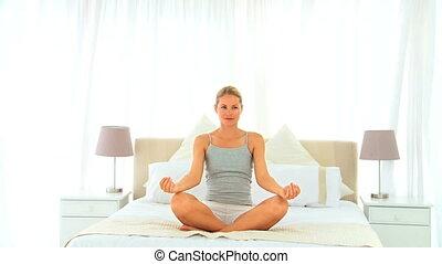 Blonde woman doing the lotus positi