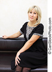 blonde woman dressed in black dress sits on black leather couch