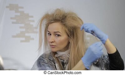 Blonde woman dyes her hair herself. Coloring hair at home. -...