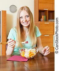 blonde woman eating fruit salad at home