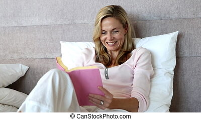 Blonde woman enjoying a book sitting in her bed