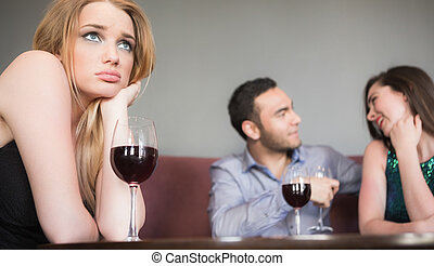 Blonde woman feeling jealous of couple flirting beside her...