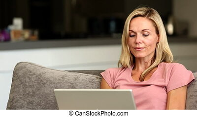 Blonde woman happy winning online at home on the couch