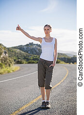 Blonde woman hitching a lift on a deserted road
