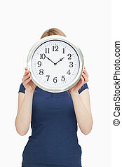Blonde woman holding a clock in front of her face