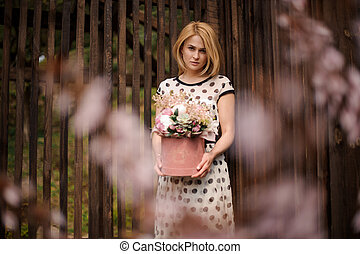 Blonde woman holding a flower box standing on the background of wooden fence and pink blooming tree