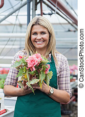 Blonde woman holding a flower working in garden center