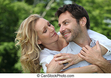 Blonde woman hugging man from behind