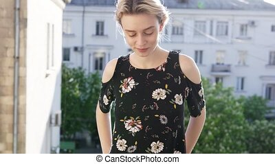 blonde woman in a dress with flowers on the background of the streets