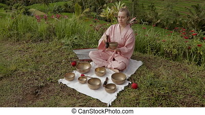 Blonde woman in a pink kimono playing on meditative Himalayan singing bowl. Sound meditation, sound healing. She is sitting on a green grass in Jatiluwih rice terraces . High quality 4k footage