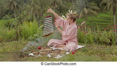 Blonde woman in a pink kimono playing on meditative Himalayan Tibetan music instrument. Sound yoga, healing, meditation. Rice fields, Jatiluwih, Bali, Indonesia High quality 4k footage