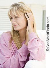 Blonde woman in a pink sweater posing outdoors