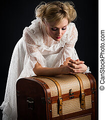 blonde woman in a white dress with wooden chest