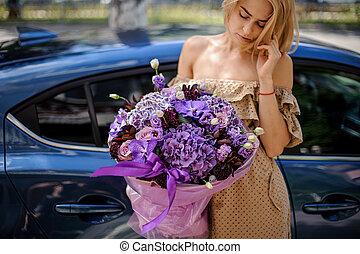 Blonde woman in beige dress holding a big bouquet of flowers in purple tones