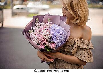 Blonde woman in beige dress holding a romantic bouquet of flowers in purple tones