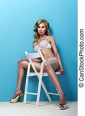 Blonde Woman In Bikini Sitting On Chair On Blue Background