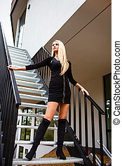 Blonde woman in black short dress on staircase