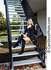 Blonde woman in black short dress sitting on staircase