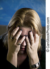 Close up of blonde woman in a studio setting hiding her face in her hands.