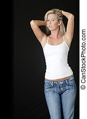 Blonde woman in jeans and white tank top on black background