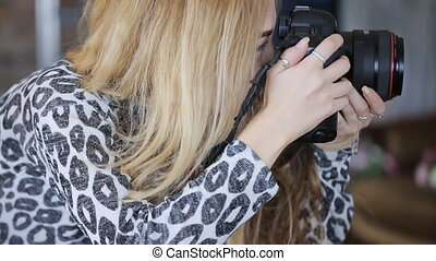 Blonde woman in leopard blouse takes photos and actively moves