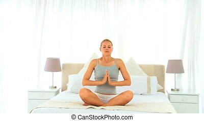 Blonde woman in lotus position