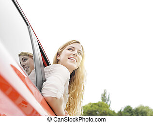 Blonde woman in red car.