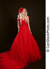 Blonde woman in red dress and elegant hat isolated on studio black background. Beautiful blond girk with long wavy hair posing in prom gown.