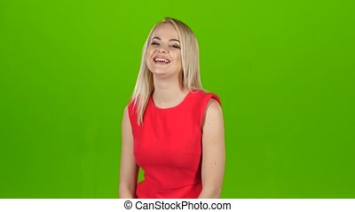Blonde woman in red dress sincerely, contagious laughs. Green screen