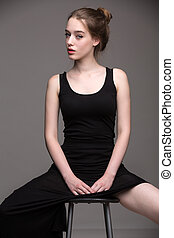 Blonde woman in sexy black dress sitting on a chair