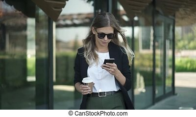 Blonde woman in sunglasses with coffee walking and looking at smartphone