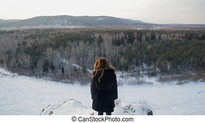 Blonde woman in winter is back in front of a mixed forest.