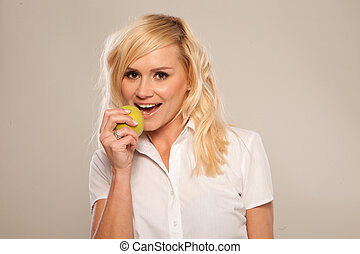 Blonde woman is preparing to bite a green apple