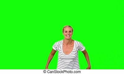 Blonde woman jumping against green screen in slow motion