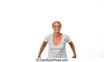 Blonde woman jumping against white background in slow motion