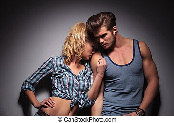 blonde woman kissing her lover on shoulder - blonde woman...