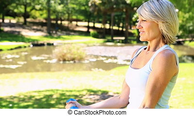 Blonde woman lifting dumbbells in  the park