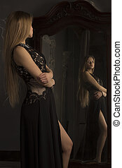 Blonde woman looking herself reflection in mirror